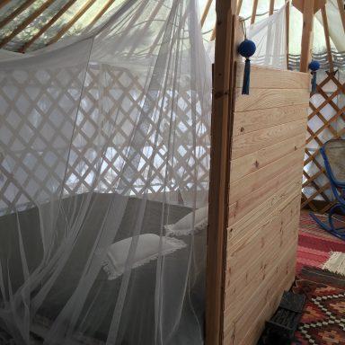 Double bed with mosquito net in the blue door yurt.
