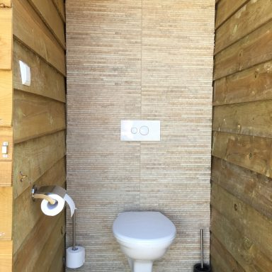 The toilet on the right side of the utility hut.