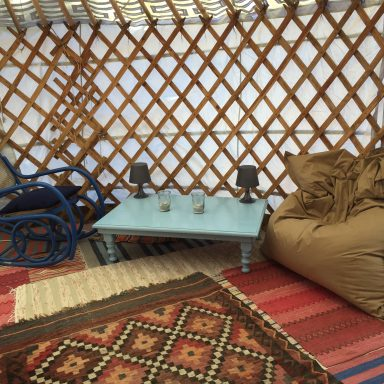 Area for relaxation in the blue door yurt - rocking chair and bean bag.