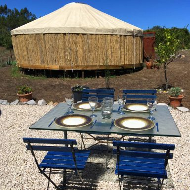 The dining table outside the utlity hut and the larger red door yurt behind it.