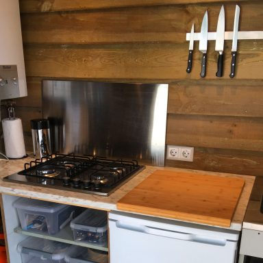 Well equipped kitchen with a gas stove, fridge and utensils.