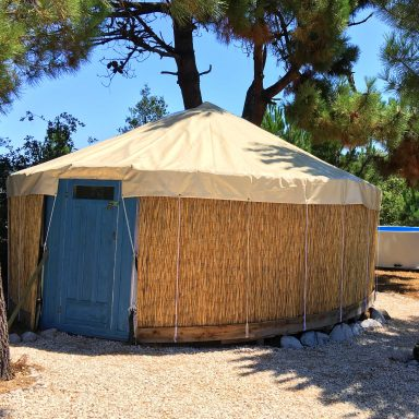 The blue door yurt with the pool behind it.