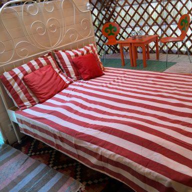 Double bed inside the red door yurt.