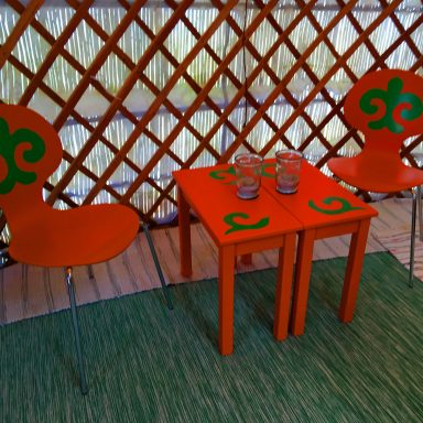 Colourful chairs and tables placed on the multi-coloured rugs of the red door yurt floor.