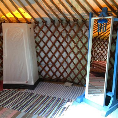Hanging closet and mirror in the larger red door yurt.